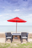 Outdoor table set, beach chairs and red umbrella with beautiful Royalty Free Stock Photo