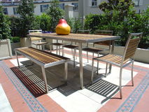 Outdoor table setting. With teak and stainless steel table, chairs and bench Royalty Free Stock Image