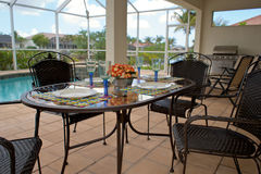Outdoor table setting for dinner. A table is set for dinner on an outside patio or lanai with swimming pool in background, the patio is screened in Stock Images