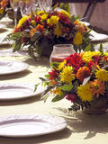 Outdoor Table setting with flowers. In fall colors red yellow golds and orange with white plates crystal glasses in the background Stock Image