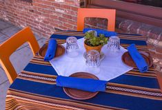 Outdoor Table Setting for Four. Table set for four including chairs, plates, napkins and glasses with colorful table cloth and plant center piece Royalty Free Stock Photo
