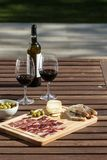 Outdoor table setting red wine cheese and bread. Outdoor table setting with red wine cheese and bread stock image