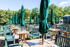 Outdoor Tables with Green Umbrellas and Chairs Stock Photo