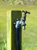 Outdoor tap. Dripping outdoor tap in field. Mouted on a wooden post Royalty Free Stock Images