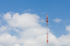 Outdoor tele communication red and white tower blue sky and clou Stock Photos