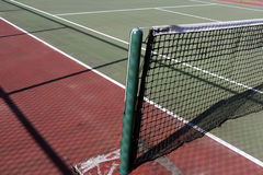 Outdoor tennis court. An outdoor public tennis court with green post and net Royalty Free Stock Image