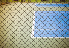 Outdoor tennis sport court behind wired fence Royalty Free Stock Photos