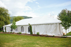 Outdoor Tent Wedding with Mountains. A summer outdoor wedding reception tent surrounded by grass and trees with a mountain in the background and blue sky Stock Image