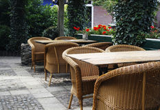 Outdoor terrace. Outdoor cafe with rotan chairs and wooden tables Royalty Free Stock Images