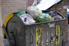 Outdoor trash bin with food waste. Not sorted garbage, yard, stench, filth. Carelessness. Steel container stock image