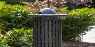 Outdoor trash can with plants in the background. Close up view of a gray cylindrical trash can with a black garbage bag inside on a sunny day. Leafy plants can royalty free stock image