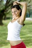 Outdoor Triceps Stretch. A young woman stretching outside in the park (shallow depth of field royalty free stock photography