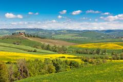 Tuscan farmhouse with green and yellow fields Stock Image