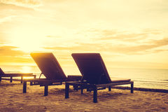 Outdoor with umbrella and chair. On beautiful tropical beach and sea at Sunset time - Vintage Filter Royalty Free Stock Image