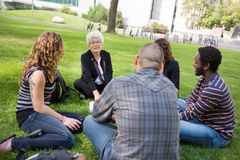 Outdoor University Class. University class taking place outdoors with small group of students Stock Photo