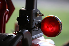 Outdoor vehicle brake light. A red brake light on a tractor with a green background stock images