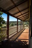 Outdoor verandah patio deck of sandstone brick cottage with picket fence in sunshine with trees in background. Outdoor verandah patio deck of sandstone brick stock photo