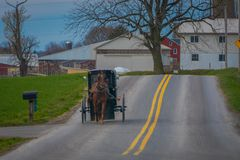 Outdoor view of Amish horse and carriage travels on a road in Lancaster County. Pennsylvania Royalty Free Stock Images