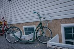 Outdoor view of amish roller bikes or scooters lean against a house royalty free stock photo