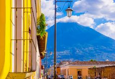 Outdoor view of balcony with some plants in a pot and publibc lamp lights with a volcano behind, partial covered with. Clouds in a gorgeous sunny day in Antigua Royalty Free Stock Photo