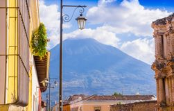 Outdoor view of balcony with some plants in a pot and publibc lamp lights with a volcano behind, partial covered with. Clouds in a gorgeous sunny day in Antigua Royalty Free Stock Image