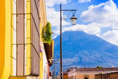 Outdoor view of balcony with some plants in a pot and publibc lamp lights with a volcano behind, partial covered with. Clouds in a gorgeous sunny day in Antigua Royalty Free Stock Photos