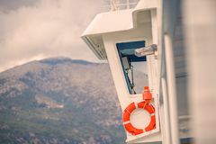 Outdoor view on captain`s cabin, glass control room and mountains view on the background. Red Life Buoy hanging under the window of captain`s cabin Stock Photography