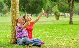 Outdoor view of daughter and father sitting in the grass and extending arms to catch something, in the park stock photo