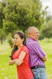 Outdoor view of father and daughter back to back each other at outdoors, in the park royalty free stock photo