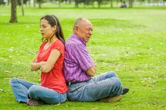 Outdoor view of father and daughter sitting in the grass and back to back each other at outdoors, in the park stock images