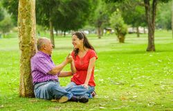 Outdoor view of father and daughter with thumps up at outdoors sitting in the ground, in the park stock photo