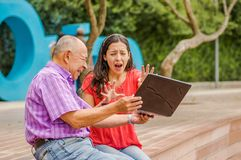 Outdoor view of father holding and computer and sacry daugher screaming afraid of his dad throw the computer in the. Ground, at park Stock Image