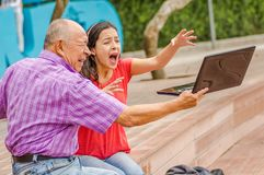 Outdoor view of father holding and computer and sacry daugher screaming afraid of his dad throw the computer in the. Ground, at park Royalty Free Stock Photography
