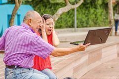 Outdoor view of father holding and computer and sacry daugher screaming afraid of his dad throw the computer in the. Ground, at park Royalty Free Stock Image
