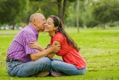 Outdoor view of father kissing her daughter with love at outdoors sitting in the ground, in the park royalty free stock photo