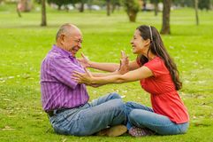 Outdoor view of father rejecting her daughter at outdoors sitting in the ground, in the park stock photography