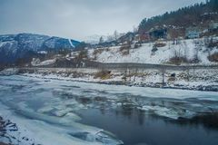 Outdoor view of frozen river with some wooden houses at one side of the road at Gol Mountain Are. A in Norway royalty free stock images