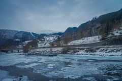 Outdoor view of frozen river with some wooden houses at one side of the road at Gol Mountain Are. A in Norway stock images