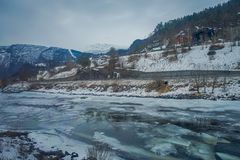 Outdoor view of frozen river with some wooden houses at one side of the road at Gol Mountain Are. A in Norway stock photography