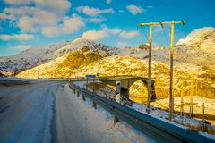 Outdoor view of frozen street and stoned bridge with some cable lines at one side of the road, during a gorgeous sunny. Day in Lofoten Islands in Norway Royalty Free Stock Image