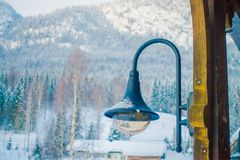 Outdoor view of light lamp close to wooden pillar. In Norway in a blurred nature snow background Stock Image