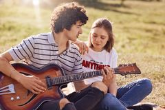 Outdoor view of lovely female and her male companion have leisure time, handsome teenager plays guitar, looks with love at his gir. Lfriend, pose on green field Stock Image