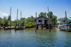 Outdoor view of old and damaged house floating in the river close to the mangroves in a gorgeopus blue asky in Krabi. Province, South of Thailand Stock Photo