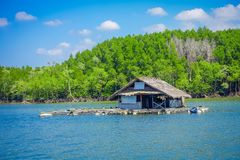 Outdoor view of old and damaged house floating in the river close to the mangroves in a gorgeopus blue asky in Krabi. Province, South of Thailand Stock Images