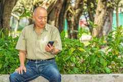 Outdoor view of old man sits on bench with a cellphone in his hand and enjoying the nature and having a good rest. All Royalty Free Stock Photos