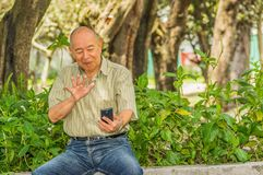 Outdoor view of old man sits on bench and saying hello on video cam with cellphone in his hand, enjoying the nature and Royalty Free Stock Image