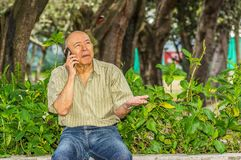 Outdoor view of old man sits on bench using his cellphone and enjoying the nature. All problems left behind Royalty Free Stock Images