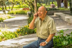 Outdoor view of old smiling man sits on bench using his cellphone and enjoying the nature. All problems left behind Royalty Free Stock Image