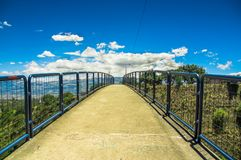Outdoor view of pedestrian bridge over a road to visit the municipal dump in a beautiful day in the city of Quito Royalty Free Stock Image