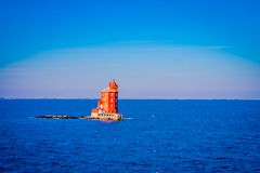 Outdoor view of the red lighthouse on the Norwegian sea over a rock. In a gorgeous blue sky in Hurtigruten Norway Royalty Free Stock Photo